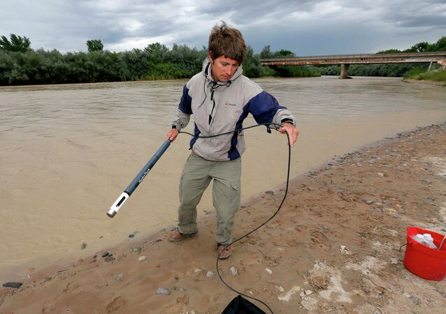 An official with the Utah Department of Environmental Quality takes a pH level reading from a probe in the San Juan River in Utah.