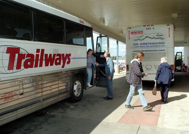 Passengers depart a bus.