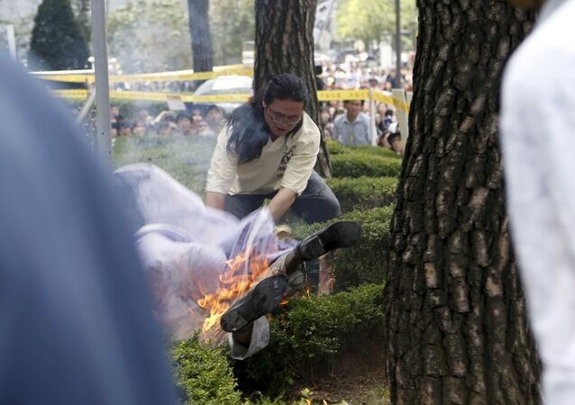 A man attempts to put out flames from another man (bottom) who set himself on fire during a weekly anti-Japan rally to demand for an official apology and compensation from the Japanese government in front of the Japanese embassy in Seoul, South Korea, August 12, 2015
