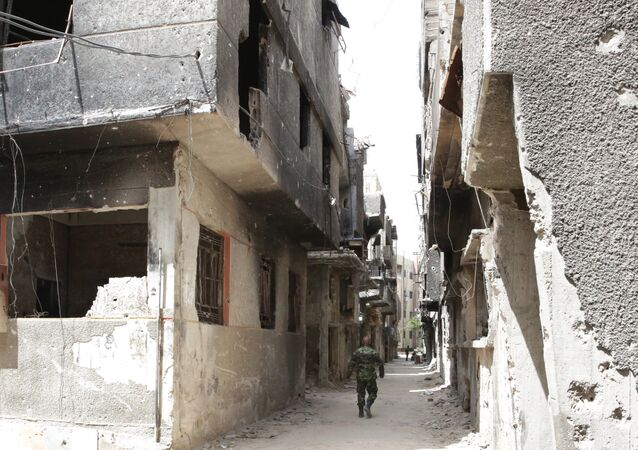 FILE PHOTO. A soldier walks down an alley through heavy damage during a government escorted visit to Yarmouk refugee camp in Damascus, Syria, Thursday, April 9, 2015