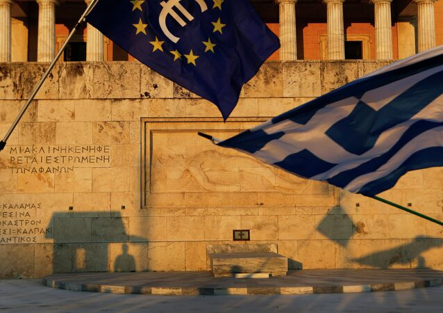 Pro-Euro demonstrators wave a Greek flag, right, and a European Union flag