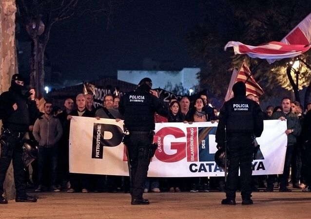 Policemen stand in front of supporters of the anti-Islam group 'Pegida' (Patriotic Europeans Against The Islamization Of The West) during a demonstration in L' Hospitalet del Llobregat on March 11, 2015