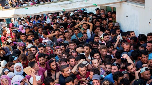 Syrian migrants and refugees gather at a makeshift migrant detention center at Kos' abandoned football stadium after crossing from Turkey, at the southeastern island of Kos, Greece, Wednesday, Aug. 12, 2015. - Sputnik International