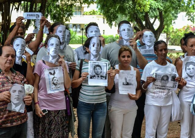 Cuban dissidents pose wearing masks depicting US President Barack Obama and holding pictures of imprisoned dissidents as they protest against the reopening of the US embassy in the island, during a meeting of the Ladies in White human rights group in a park of Havana, on August 9, 2015