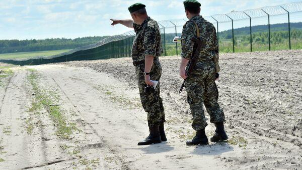 Ukrainian border guards patrol on July 2, 2015 along the barbed wire fence on the Senkivka border post, around 200 kilometres (125 miles) north of the Ukrainian capital Kiev. - Sputnik International