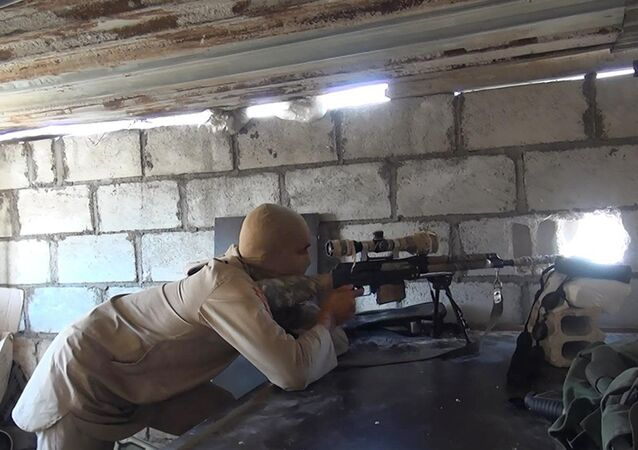 This picture released on July 13, 2015 by the Rased News Network, a Facebook page affiliated with Islamic State militants, shows an Islamic State militant sniper in position during a battle against Syrian government forces, in Deir el-Zour province, Syria