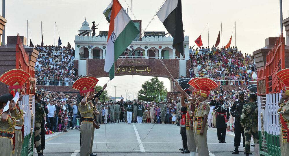 Indian and Pakistani flags are lowered during a daily retreat ceremony at the India-Pakistan joint border check post of Attari-Wagah near Amritsar, India, Tuesday, July 21, 2015