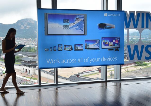 A woman walks past a billboard for Windows 10, the latest operating system from US software giant Microsoft, during a launch event in Seoul on July 29, 2015
