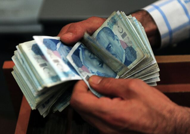 An exchange office worker counts Turkish lira banknotes in Istanbul