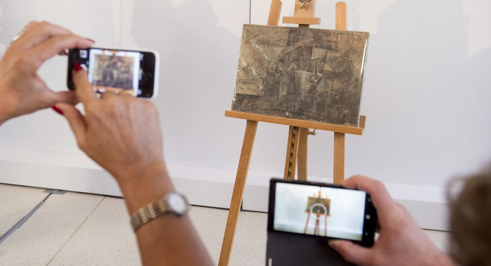 People photograph a Pablo Picasso painting, La Coiffeusse, or The Hairdresser, during a repatriation ceremony at the French Embassy in Washington, DC, August 13, 2015