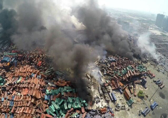 This screen grab taken from AFPTV shows an aerial image taken on August 13, 2015 of smoke rising from debris the day after a series of explosions hit a chemical warehouse in the city of Tianjin, in northern China