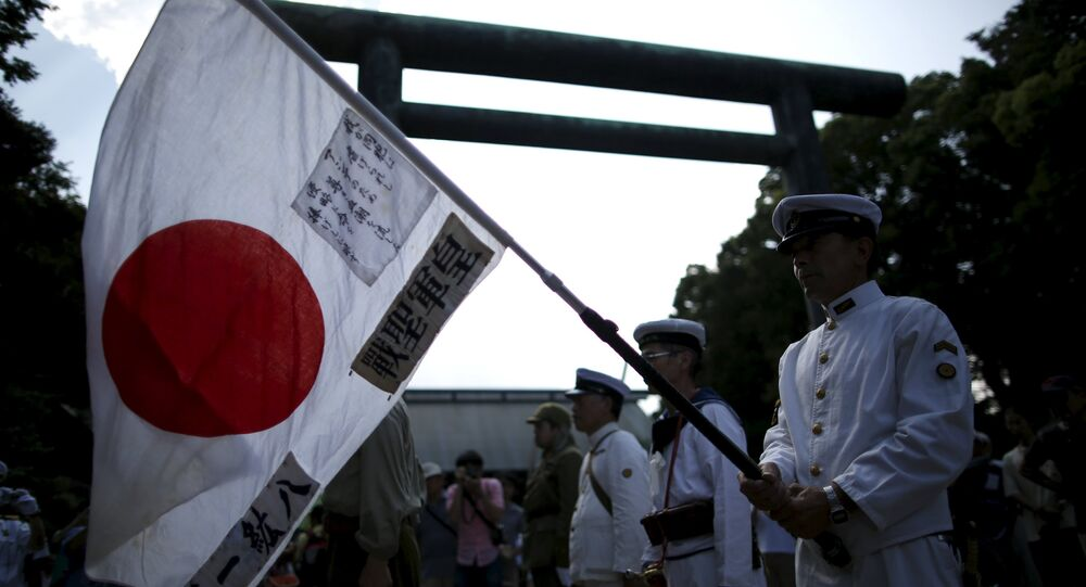 Men dressed as Japanese imperial army soldiers and sailors hold the Japanese national flag at Yasukuni Shrine in Tokyo August 15, 2015, to mark the 70th anniversary of Japan's surrender in World War Two