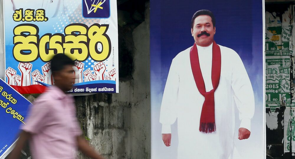 A man walks past a poster of Sri Lanka's former president Mahinda Rajapaksa ahead of a general election, in Galle August 14, 2015