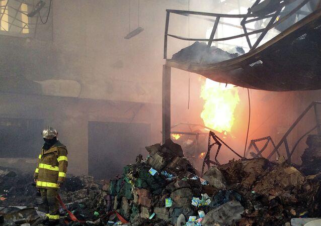 A Thai fireman (L) stands inside a scrap metal warehouse after an explosion