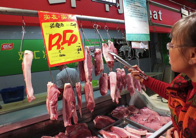 A customer selects the pieces of pork, supplied by Shuanghui, which controls China's largest meat-processing company, at a supermarket in Yichang, central China's Hubei province