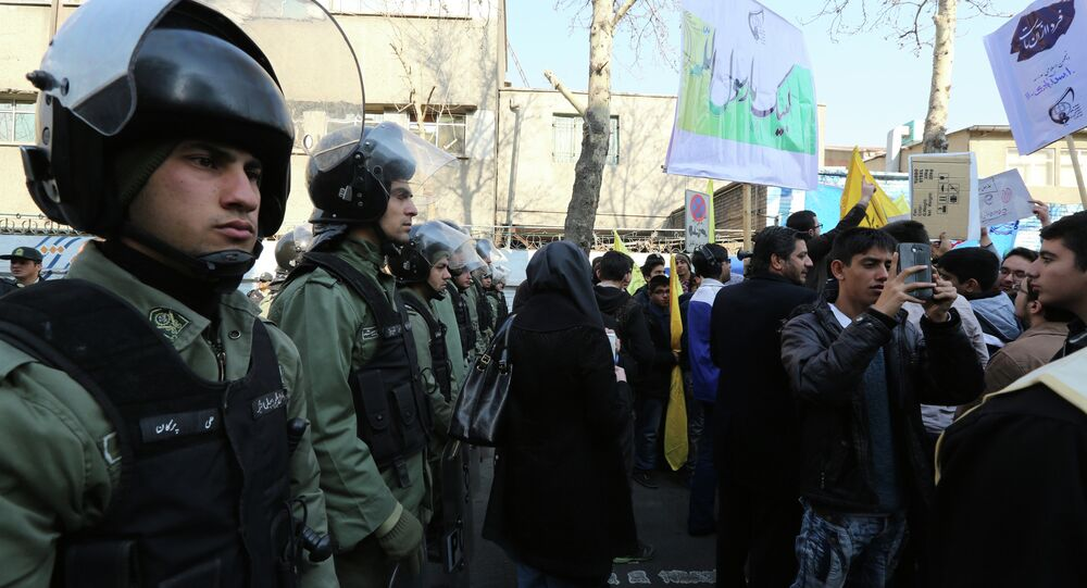 Iranian security forces stand guard outside the French embassy in Tehran as demonstrators protest on January 20, 2015