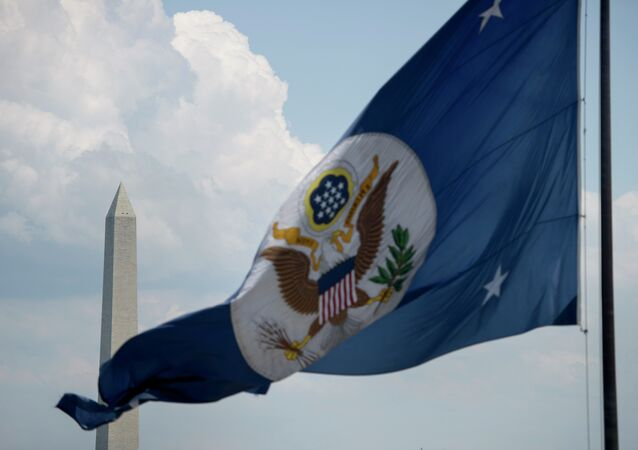 The Washington Monument is seen beyond the US State Department's flag.