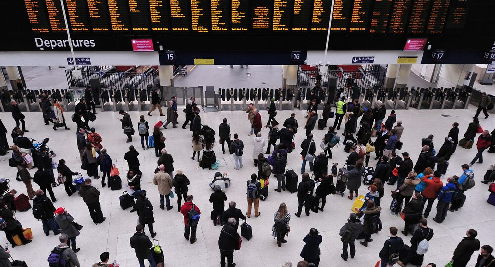 People wait with their luggage by the departure boards in Waterloo train station in central London