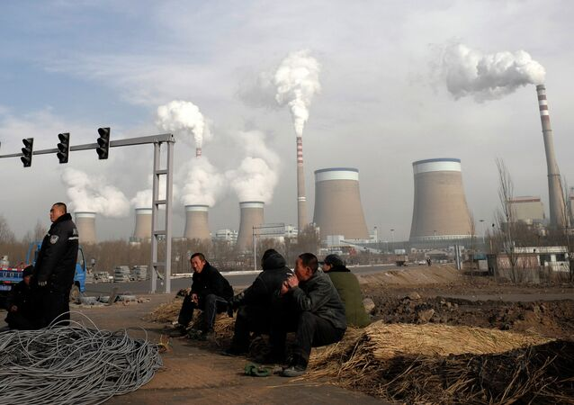 Chinese workers take a break in front of the cooling towers of a coal-fired power plant in Dadong, Shanxi province, China