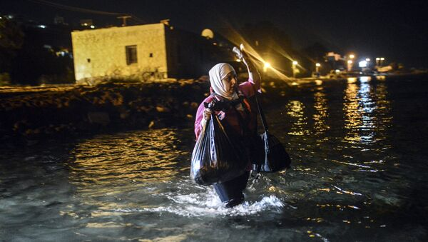 A migrant walks to a boat to reach the Greek island of Kos on early August 18, 2015. - Sputnik International