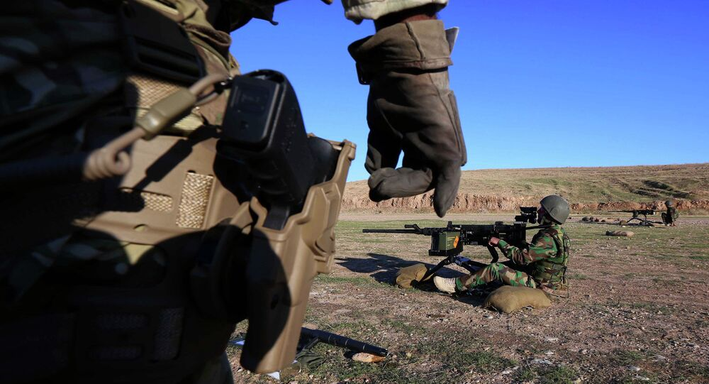 British military advisers instruct Kurdish Peshmerga fighters during a training session at a shooting range on the outskirts of Arbil, the capital of the autonomous Kurdish region of northern Iraq