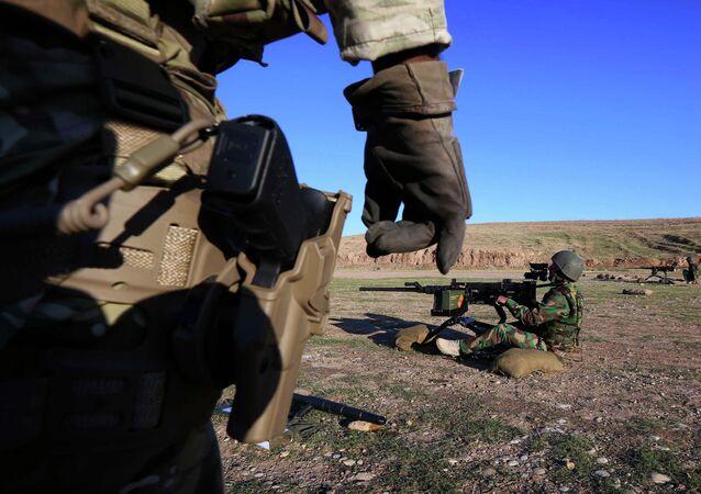 British military advisers instruct Kurdish Peshmerga fighters during a training session at a shooting range on the outskirts of Arbil, the capital of the autonomous Kurdish region of northern Iraq