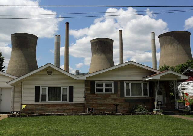 The John Amos coal-fired power plant is seen behind a home in Poca, West Virginia