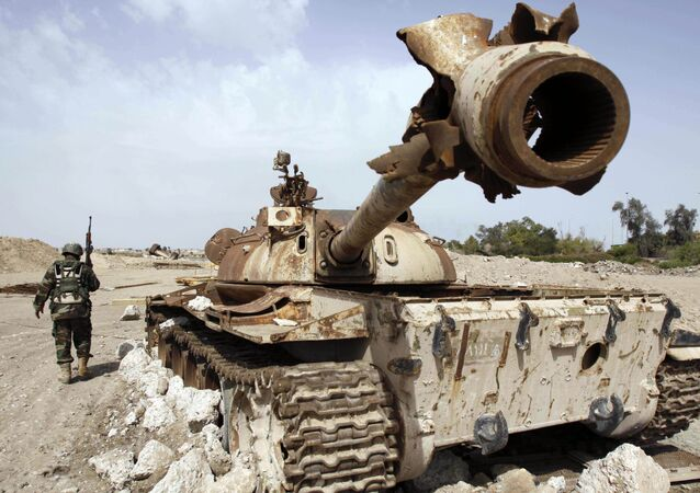 An Iraqi soldier is seen near an Iraqi Army tank, which was destroyed in the US-led invasion, in Basra, Iraq's second-largest city, 550 kilometers (340 miles) southeast of Baghdad, Iraq, Thursday, April 9, 2009