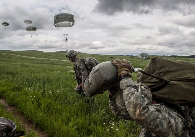 US para-troopers of the Army's 4th 25 Infantry Brigade Combat Team (Airborne), part of the NATO-led peacekeeping mission in Kosovo (KFOR) jump with parachute during a military drill near the village of Ramjan on May 27, 2015