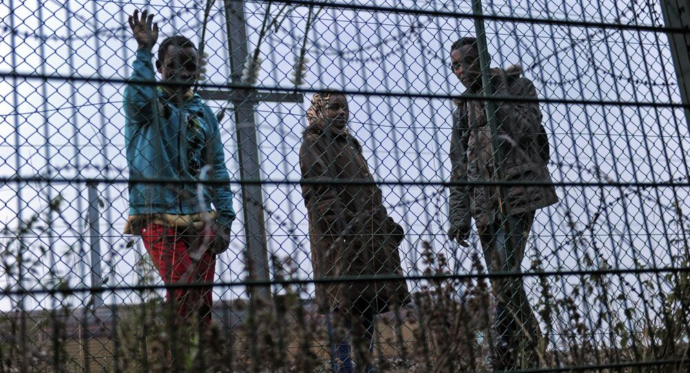 Migrants wait along the railway tracks of the Eurotunnel terminal at the Calais-Frethun station outside the northern French port of Calais on August 13, 2015