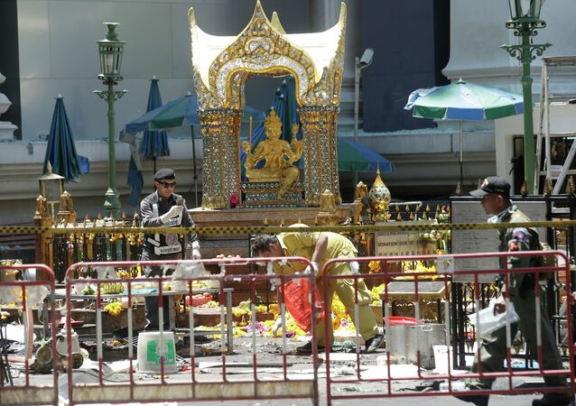 Police and officials work near the statue of Phra Phrom, the Thai interpretation of the Hindu god Brahma, at the Erawan Shrine at Rajprasong intersection the day after an explosion in Bangkok, Thailand, Tuesday, Aug. 18, 2015