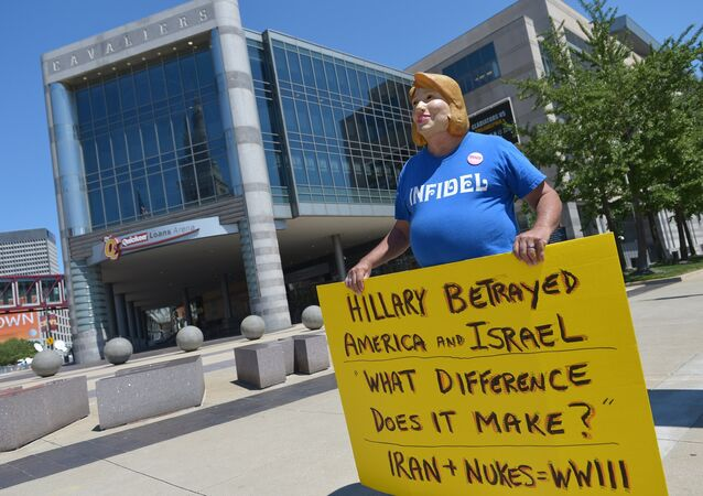 Protestor Bob Kunst of Miami, wears a Hillary Clinton mask while demonstrating outside of the Quicken Loans Arena on August 5, 2015 in Cleveland, Ohio
