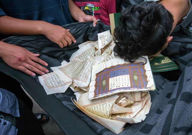 Refugees bow over ripped out pages from a Koran in a first registration center for refugees in Suhl, eastern Germany, on August 20, 2015