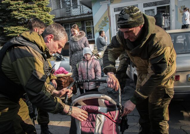 Militia of the Angel volunteer peacekeeping unit from the Donetsk and Luhansk People's Republics evacuate a woman and a child from the city of khartsyzsk