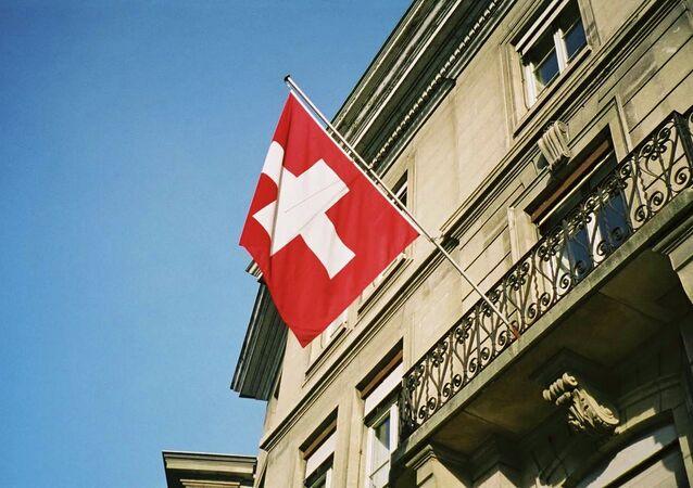 Swiss flag fluttering in the sunshine in Geneva