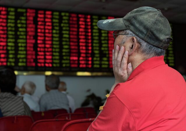 This photo taken on August 13, 2015 shows investors monitoring screens showing stock market movements at a brokerage house in Shanghai