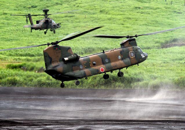 Тяжелый транспортный вертолет CH-47J Chinook в сопровождении ударного вертолета Apache на ежегодных японских военных учениях