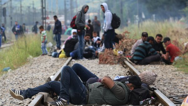 Migrants rest while waiting to pass the Greek-Macedonian border, guarded by Macedonian police near the town of Idomeni, northern Greece, on August 21, 2015 - Sputnik International