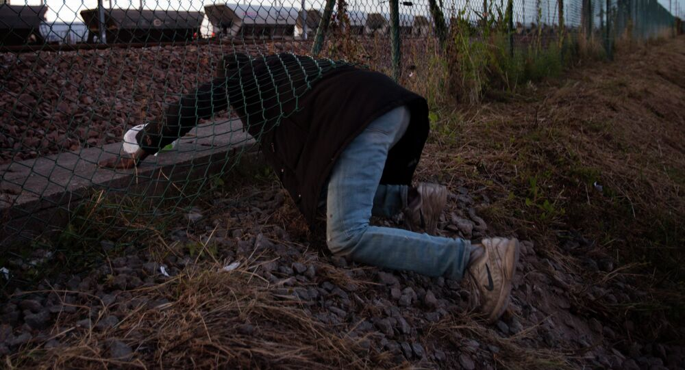 A migrant crawls under a fence as he attempts to access the Channel Tunnel in Calais, northern France, Saturday, Aug. 8, 2015