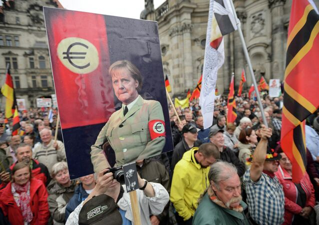 Supporters of the German right-wing movement PEGIDA (Patriotic Europeans Against the Islamisation of the Occident) hold up a poster showing German Chancellor Angela Merkel in a uniform with an Euro-logo-armband as they attend a PEGIDA rally on June 1, 2015 in Dresden, eastern Germany.