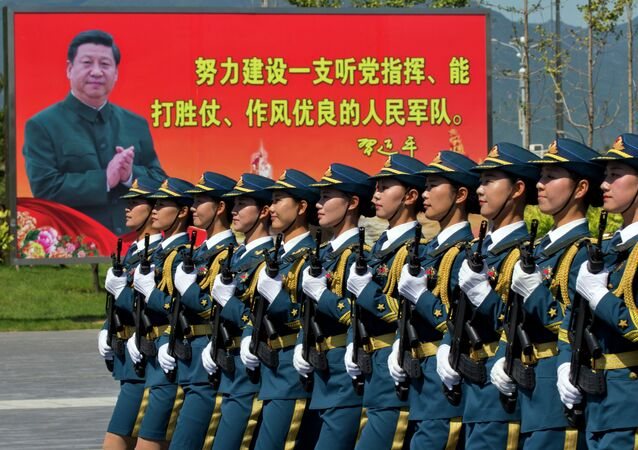 "Chinese female troops practice marching near a billboard showing Chinese President Xi Jinping and the slogan Strive to build a People's Liberation Army that obeys the Party, Wins the war and has outstanding work style"" at a camp on the outskirts of Beijing, Saturday, Aug. 22, 2015"