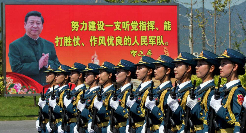 """Chinese female troops practice marching near a billboard showing Chinese President Xi Jinping and the slogan Strive to build a People's Liberation Army that obeys the Party, Wins the war and has outstanding work style"""" at a camp on the outskirts of Beijing, Saturday, Aug. 22, 2015"""
