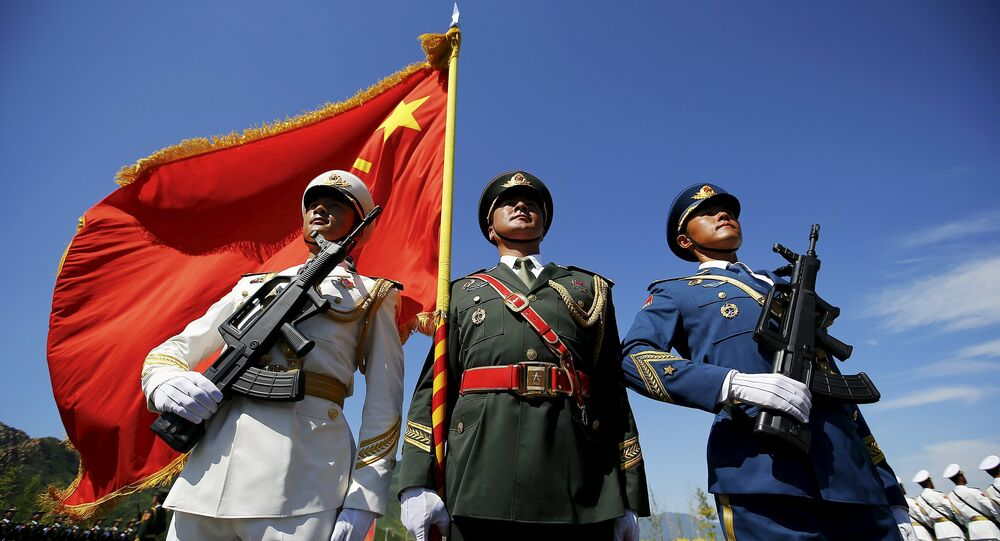 Officers and soldiers of China's People's Liberation Army hold a flag and weapons during a training session for a military parade to mark the 70th anniversary of the end of World War Two, at a military base in Beijing, China, August 22, 2015