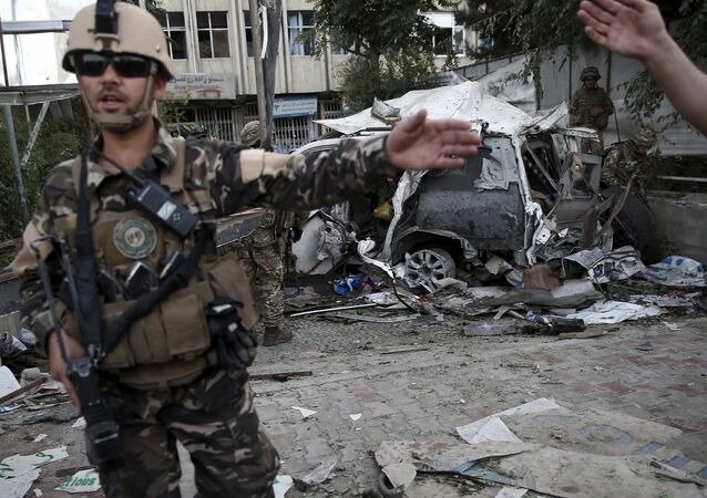 Members of Afghan security forces keep watch in front of a damaged car that belongs to foreigners after a bomb blast in Kabul, Afghanistan August 22, 2015.