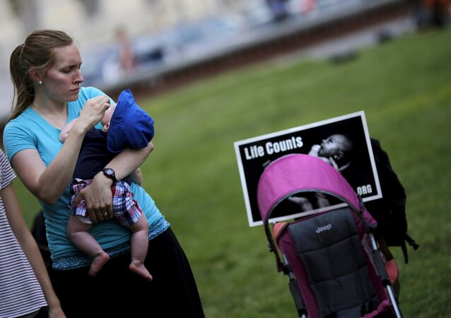A woman holds her baby as she attends a Women Betrayed Rally to Defund Planned Parenthood at Capitol Hill in Washington. (File)