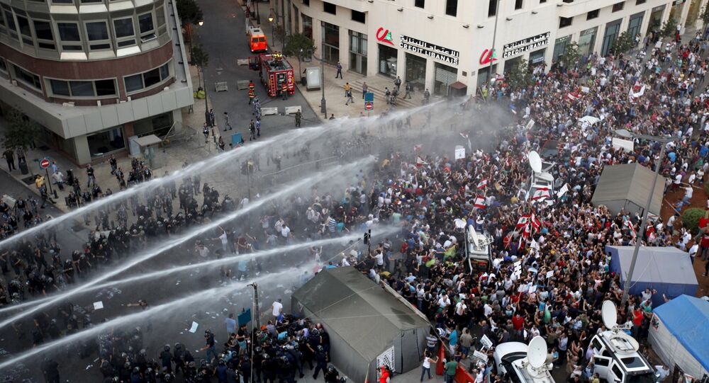 Lebanese protesters are sprayed with water during a protest against corruption and rubbish collection problems near the government palace in Beirut