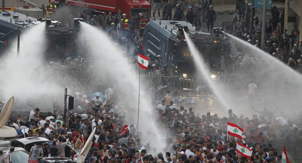 Lebanese protesters are sprayed with water during a protest against corruption and against the government's failure to resolve a crisis over rubbish disposal, near the government palace in Beirut, Lebanon August 23, 2015
