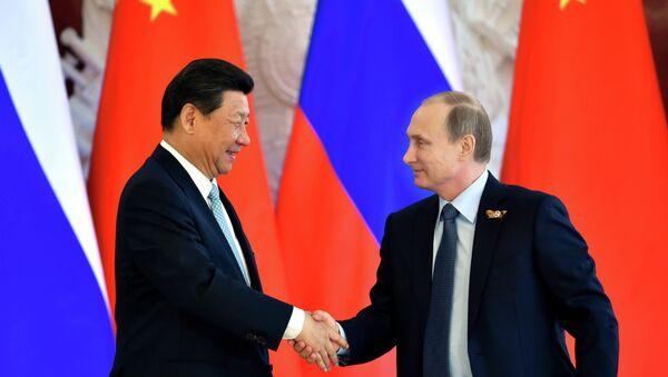 Russian President Vladimir Putin (R) shakes hands with his Chinese counterpart Xi Jinping - Sputnik International