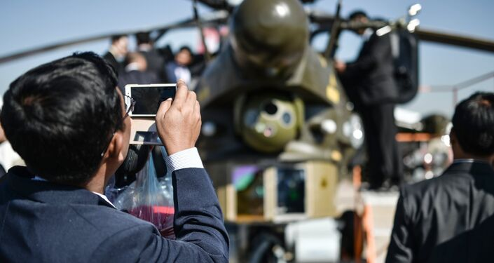 Visitors look at a Mil Mi-28 NE attack helicopter during the International Aerospace Salon MAKS 2015