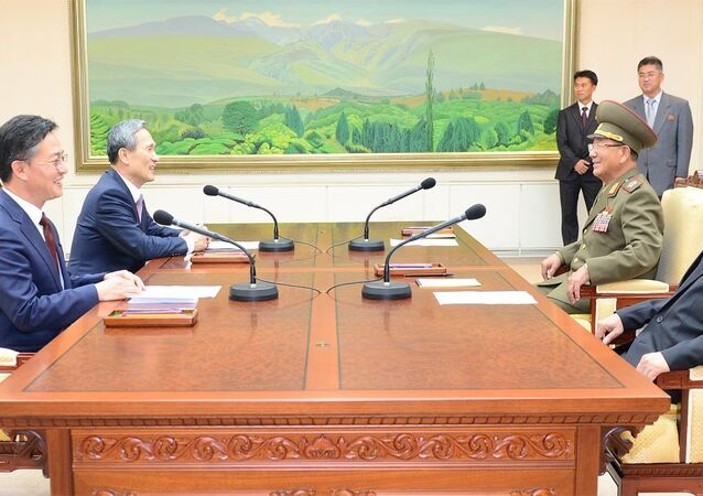 South Korean National Security Adviser Kim Kwan-jin (2nd L), South Korean Unification Minister Hong Yong-pyo (L), Secretary of the Central Committee of the Workers' Party of Korea Kim Yang Gon (R), and Hwang Pyong-so (2nd R), the top military aide to the North's leader Kim Jong Un, talk during the inter-Korean high-level talks at the truce village of Panmunjom inside the Demilitarized Zone separating the two Koreas, in this picture provided by the Unification Ministry and released by Yonhap on August 25, 2015